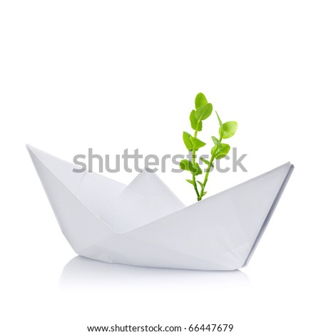 Paper ship with small green plant inside on white background - stock photo