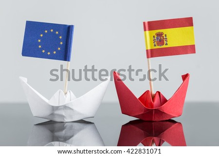 paper ship with spanish and european flag, concept shipment or free trade agreement and membership of eu