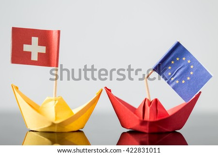 paper ship with swiss and european flag, concept shipment or free trade agreement and membership of eu, referendum