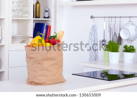 Paper shopping bag full of food on a kitchen counter