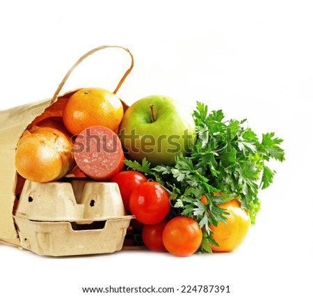 paper shopping bag full of products (bread, eggs, sausage, fruit and vegetables) - stock photo