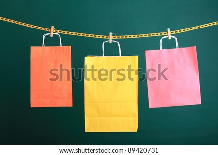 paper Shopping yellow eco orange gift bags on green background ecologocal