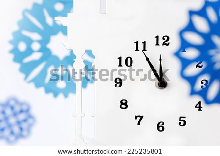 Paper snowflakes and clock. A New Years Eve