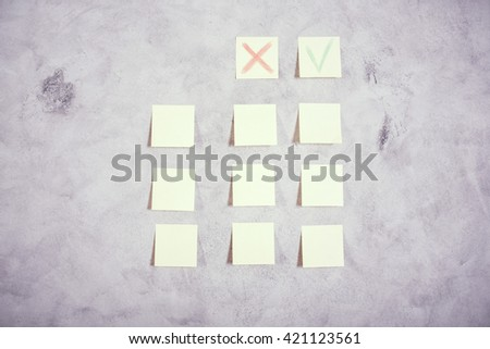 Paper stickers with red cross and green tick glued onto grey concrete wall - stock photo