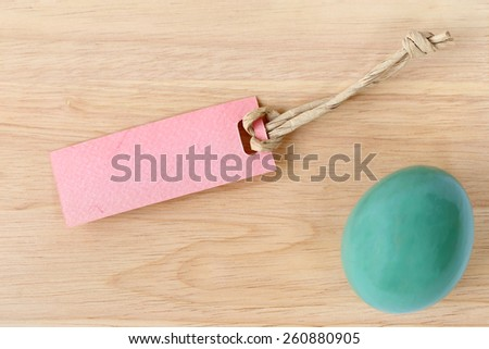 Paper tag blank for text with an easter egg on wood background. - stock photo