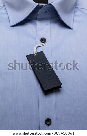 paper tag on formal blue men's shirt. Tag hang on linen thread