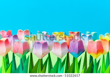 Paper tulips field with a blue background. Shallow depth of field. Focus on the front row. - stock photo
