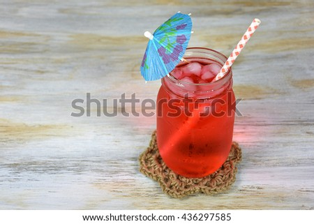 paper umbrella in cold fruit punch with gingham straw on rope coaster - stock photo
