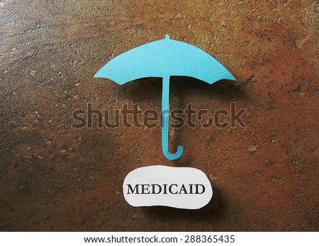 Paper umbrella over a Medicaid message                                - stock photo