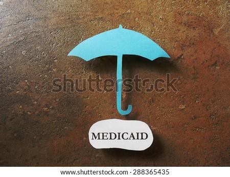 Paper umbrella over a Medicaid message                                - stock photo