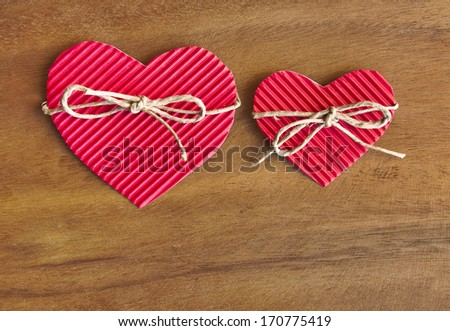 Paper valentine hearts with bow on wood