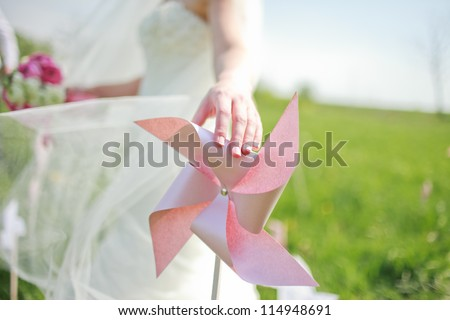 paper windmill in green grass field - stock photo