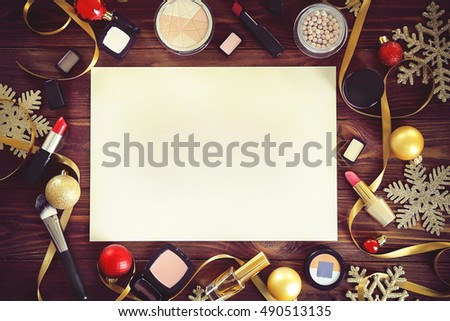 Paper with colorful makeup cosmetic and Christmas decoration on wooden background