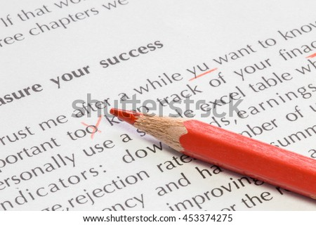 Paper with text and some wrong spelling corrected and a red pencil proofreading concept - stock photo