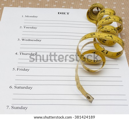 paper with week diet plan and yellow measure tape on table - stock photo