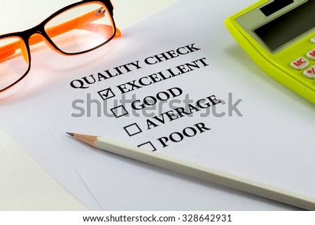 paper with word quality check and white pencil eyeglasses calculator with mark on excellent - stock photo
