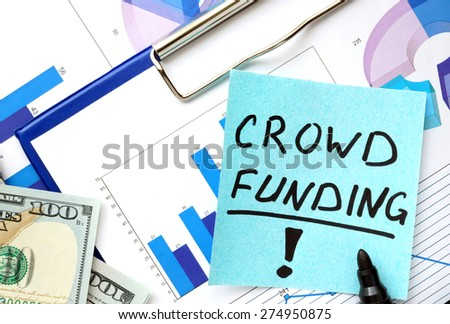 Paper with words crowd funding and graphs. Business concept.