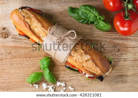 Papered vegetarian baguette submarine sandwich with grilled eggplant, pepper and feta cheese on wooden chopping board over dark background. Top view
