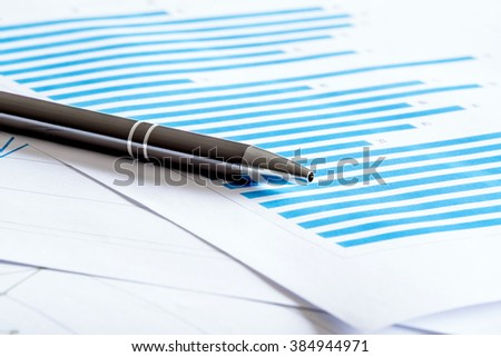 Papers with blue diagrams with a black pen