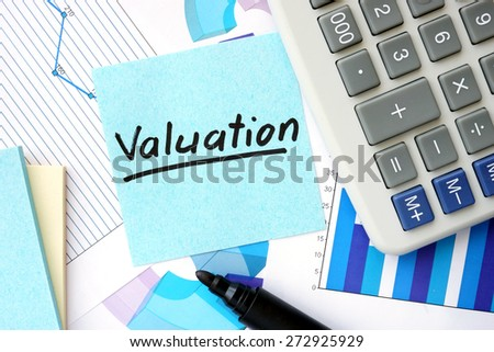 Papers with graphs, calculator and Valuation concept. - stock photo