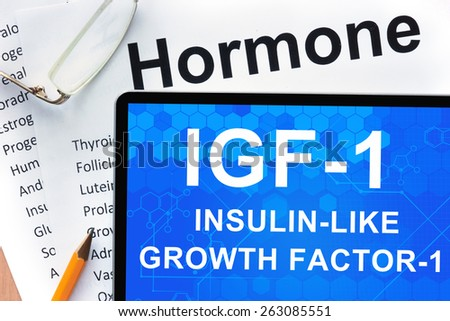 Papers with hormones list and tablet  with words Insulin-like growth factor-1 (IGF-1) .