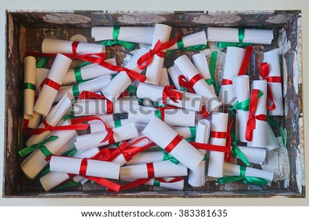 Papers with regards with green and red ribbons in vintage box