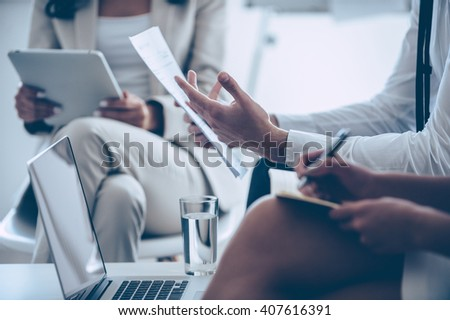 Paperwork. Close-up part of group of people brainstorming and holding documents and digital tablet while sitting at office  - stock photo