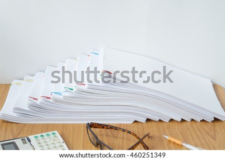 Paperwork with colorful paperclip and calculator with pen and spectacles placed on wood table.