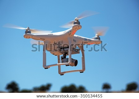 Paphos District, Cyprus - JULY 19, 2015: DJI Phantom 3 drone. Low angle view of drone flying with camera - stock photo