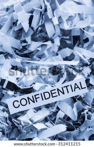 papierschnitzel tagged confidential, symbol photo for data destruction, banking secrecy and confidentiality - stock photo