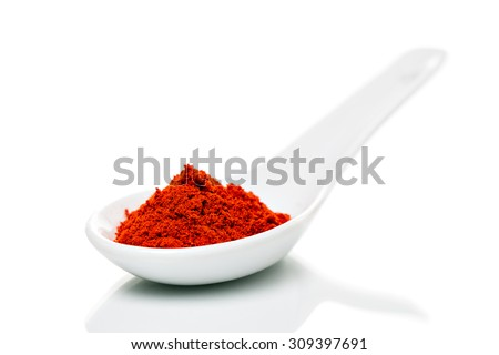 Paprika (Capsicum) powder on porcelain spoons, isolated - stock photo