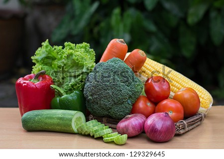 Paprika, lettuce, broccoli, carrot, corn, tomatoes, onion and slice cucumber on wood table - stock photo