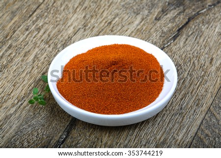 Paprika powder in the bowl on wood background