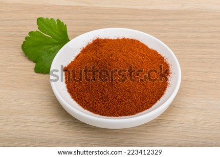 Paprika powder in the bowl on wooden background