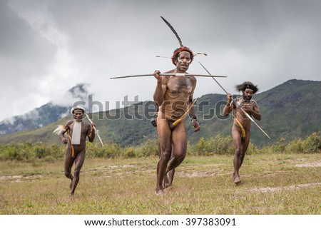 PAPUA, INDONESIA - CIRCA FEBRUARY 2016: Dani tribe men running on a field holding arrows