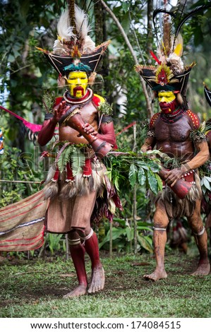 PAPUA, NEW GUINEA - OCTOBER 30: The men of the Huli tribe in Tari area of Papua New Guinea in traditional clothes and face paint on October 30, 2013.  - stock photo