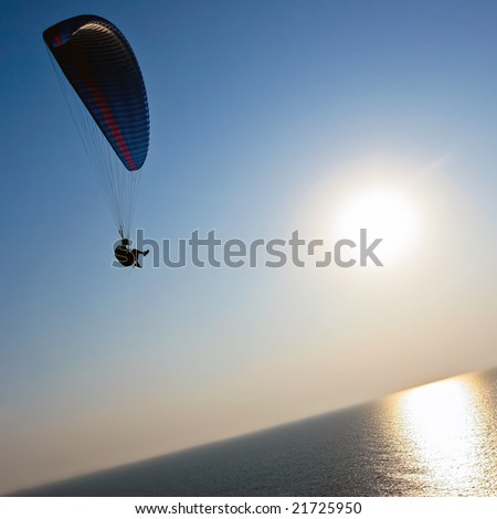 Para-glider over the sea on sunset - stock photo