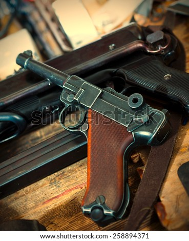 Parabellum pistol and mashinegun MP 38 in gunsmith. instagram image retro style - stock photo