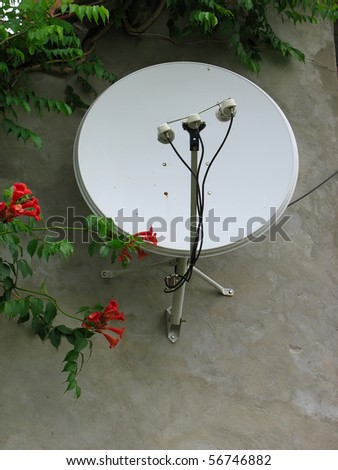 Parabolic satellite antenna on the house wall in a residential area
