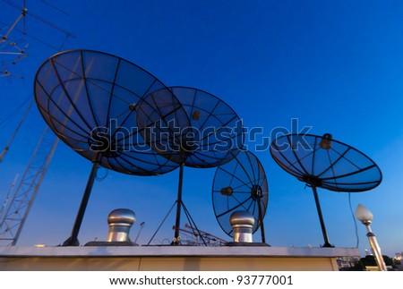 Parabolic satellite antennas with blue night background - stock photo