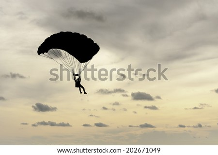 parachute at sunset silhouetted - stock photo