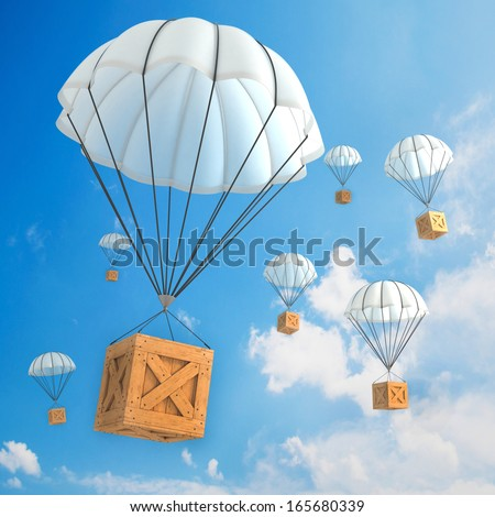 Parachute packages flying through the sky  - stock photo