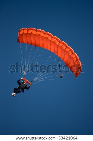 Parachuter descending with a red parachute against blue sky - stock photo
