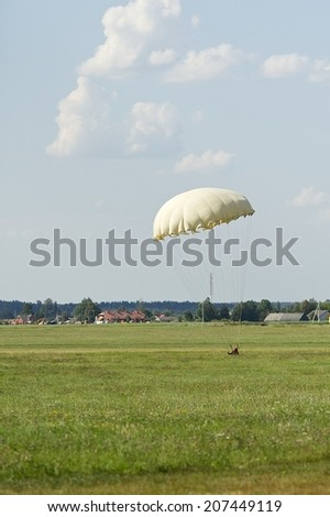 Parachutist is landing on the green field. - stock photo