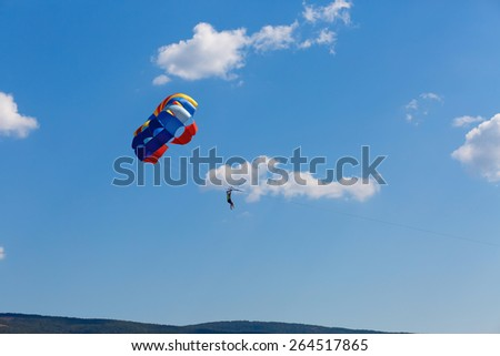 Parachutist on colorful parachute in a clear blue sky with a few clouds.