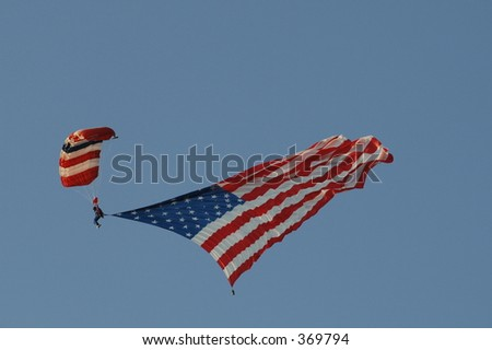 Parachutist releases a very large American flag while gliding towards earth.