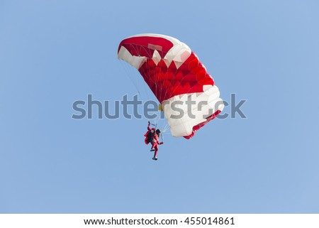 Parachutist with red parachute on a blue sky background. - stock photo