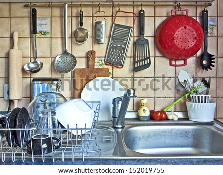 parade of useful kitchen tools, rolling pin, ladles,stainers,rasps,colanders and tableware hanging on the kitchen sink - stock photo