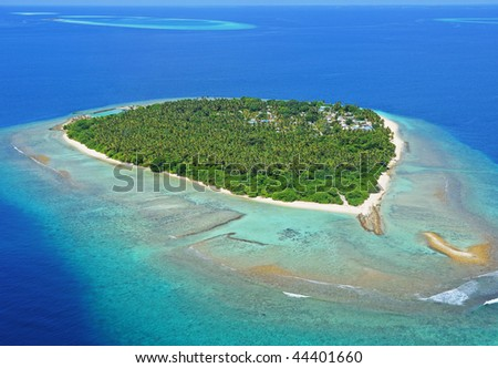 Paradisaic Maldivian island with turquoise beaches, green trees and deep blue sky. - stock photo
