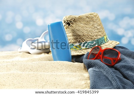 paradise beach and towel of blue and red sunglasses and hat and oil bottle  - stock photo